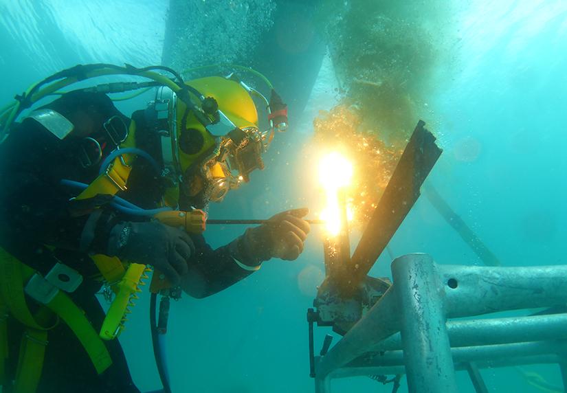 Commercial diving student welding underwater