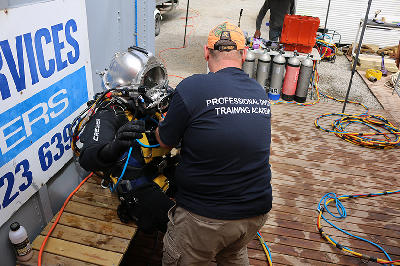 Occupational diver preparing to enter dive training tank